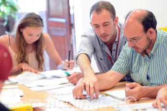 Um professor de inglês explicando algo para um aluno durante a aula