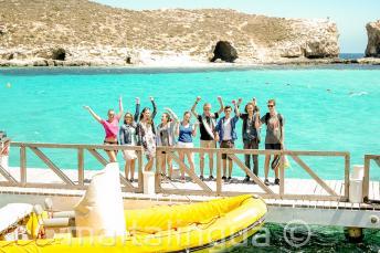 Um grupo de alunos acenando perto do barco em Blue Lagoon, Comino