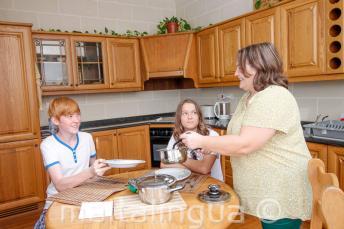 Estudantes jantando com a família de acolhimento da escola
