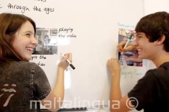 2 alunos trabalhando juntos no quadro de aulas
