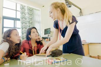 Professor explicando ponto da língua inglesa para 2 alunos