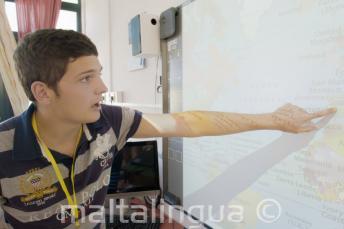 Estudante apontando para um mapa na sala de aula