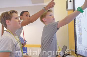 Um professor ajudando 2 alunos no quadro interactivo