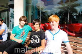 3 alunos sentado em um banco fora da residência da escola