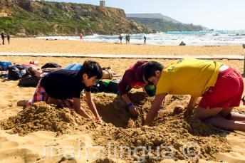Líder do grupo e crianças cavando um buraco na praia