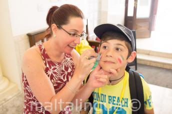 Um funcionário pintando o rosto de uma criança