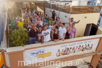 Alunos de inglês acenando no terraço da escola