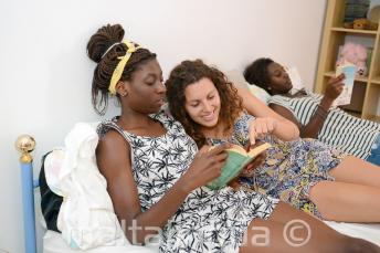 Uma aluna lendo um livro com um membro da sua familia de acolhimento