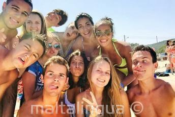Alunos da escola de língua na praia fazendo caras engraçadas