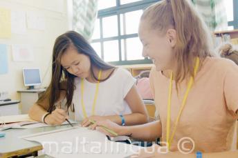 2 meninas trabalhando juntas para um exercicio de inglês