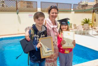 Uma mãe com seus 2 filhos que completaram um curso de línguas