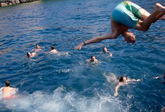 Um adolescente fazendo um salto para o mar