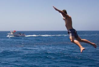 Um estudante que faz um salto do barco