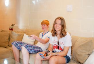 Estudantes sentados no sofá na casa da família de acolhimento
