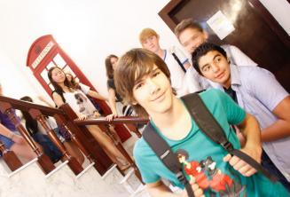 Um grupo de alunos na frente de cabines telefónicas vermelhas