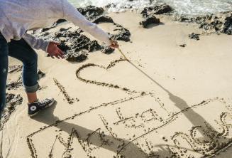 Um aluno fazendo um coração na areia Maltalingua