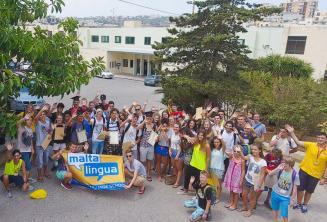 Um grupo de alunos juniores que acenam fora da escola de verão
